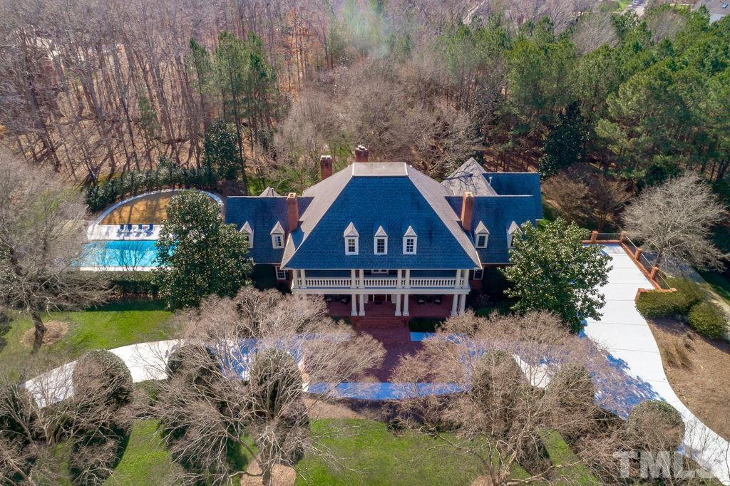 Iconic estate that pays homage to its Georgian roots! Expansive 3.5 acres in the heart of Cary, a rare find! Circular driveway leads to an impressive entry hall w/ stunning staircase, elaborate arched millwork & hardwood floors. Updated Chef's kit features large island, butlers pantry, office nook & a windowed breakfast rm w/fp overlooking the brick veranda & gorgeous wooded grounds. Resort amenities include rec rm on lower & upper levels, wet bar, pool & pool house + 4 car garage. Amazing location!!