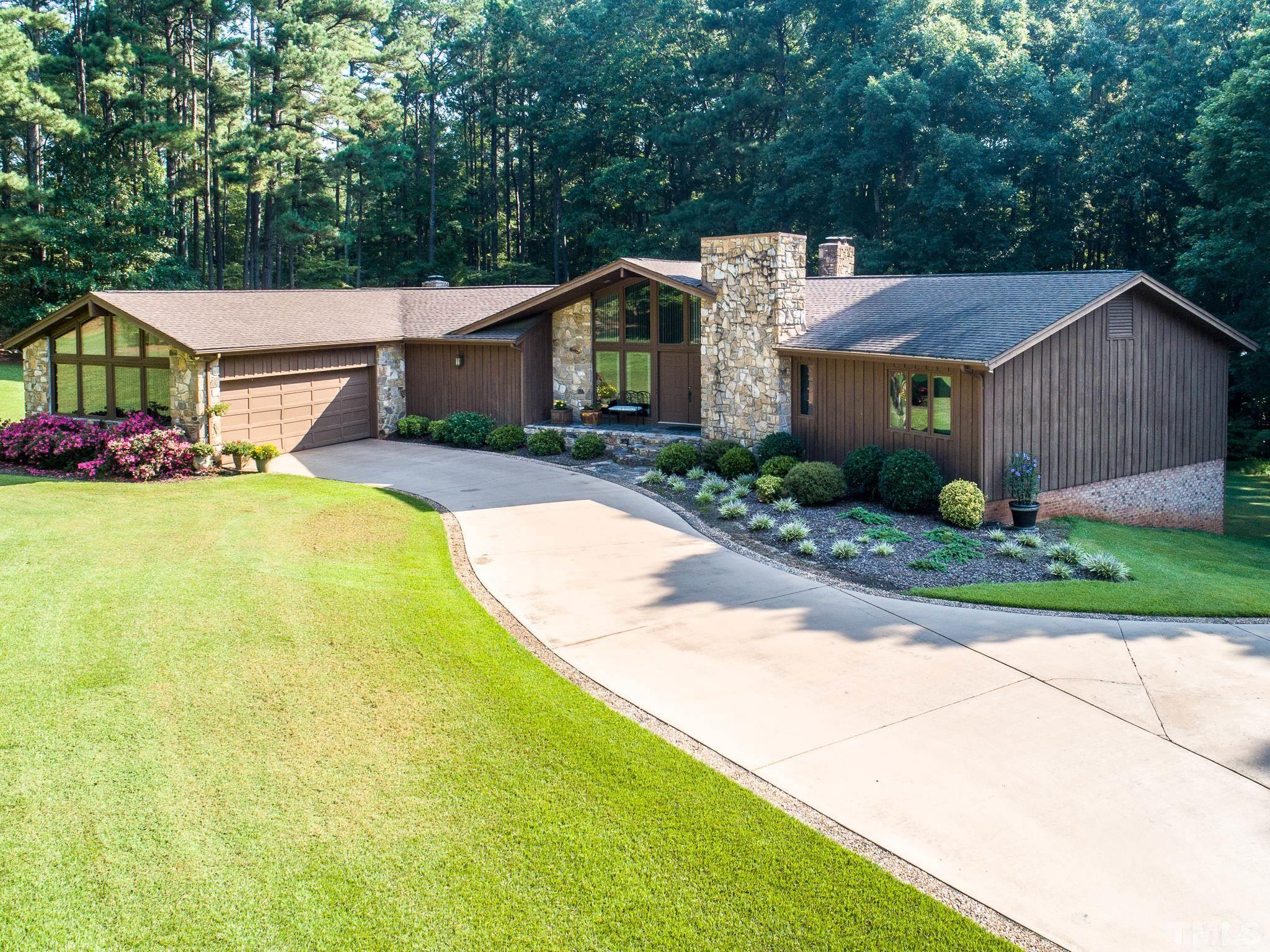 Own a one of a kind gated estate. Perfect private oasis in Cary with NO city taxes. Landscaped & partly wooded 5.6 acres. Only 1/2 mile for I-40. Backs up to Reedy Creek School & SAS property.5 bedrooms, 3 Baths, 3 fireplaces, work-out room. First floor Master suite, vaulted ceilings, lots to storage. 2 car garage. Large patio.  Wrap around deck, Water filtering system in home. 2 stalls horse barn (could be converted into a place for entertaining). Fully fenced in and gated for privacy.